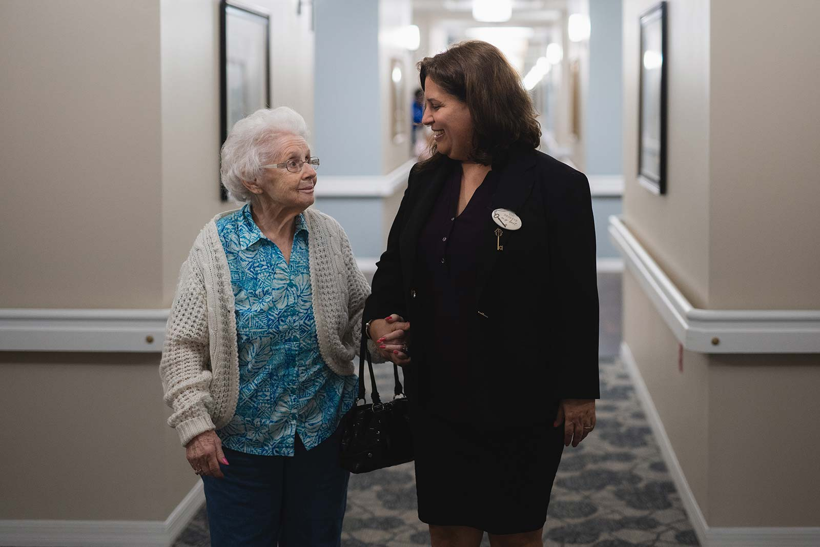 Community staff locking arms with senior woman walking down hallway at The Colonnade at Northdale assisted living and memory community in Tampa, FL